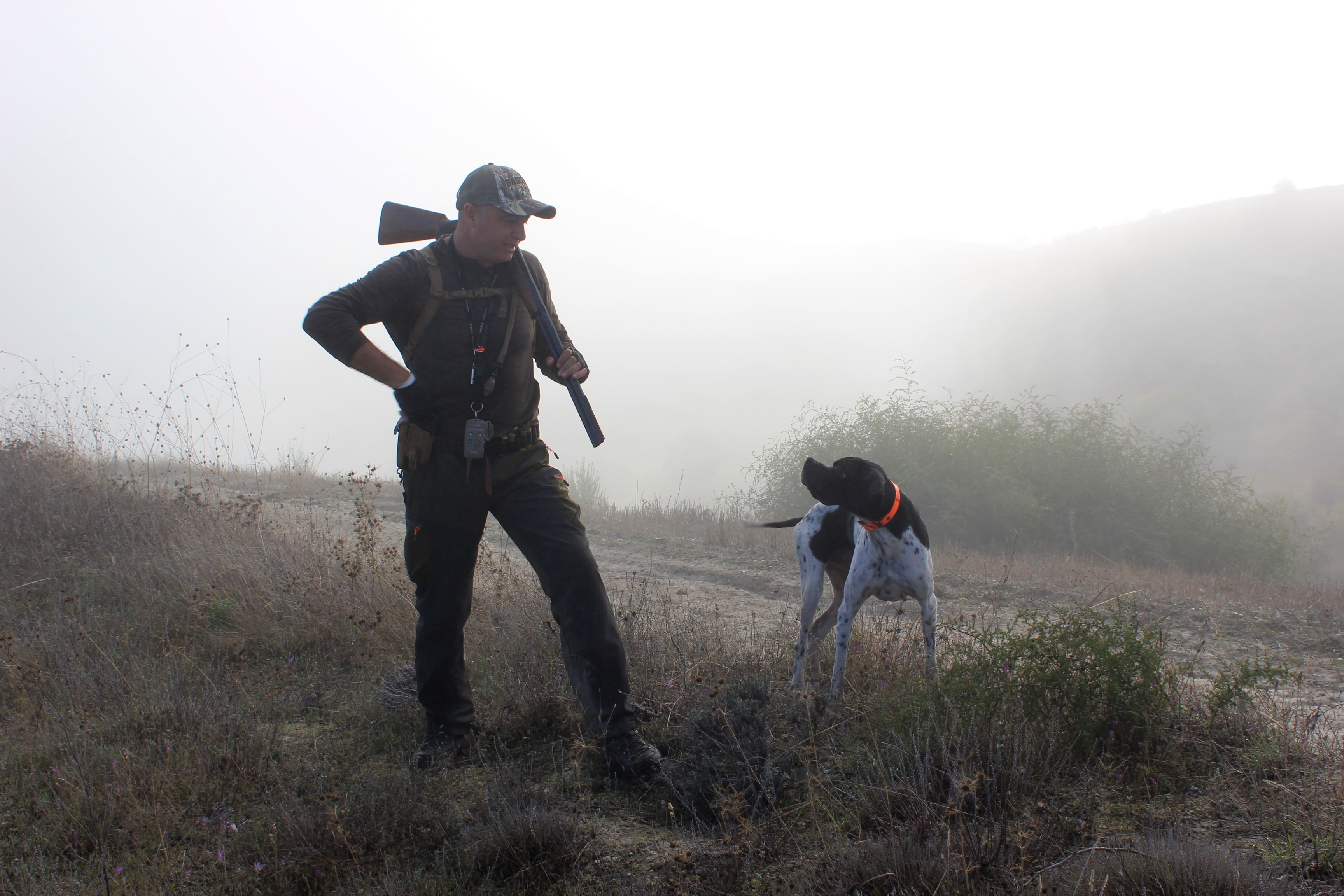 a hunter and his dog in field