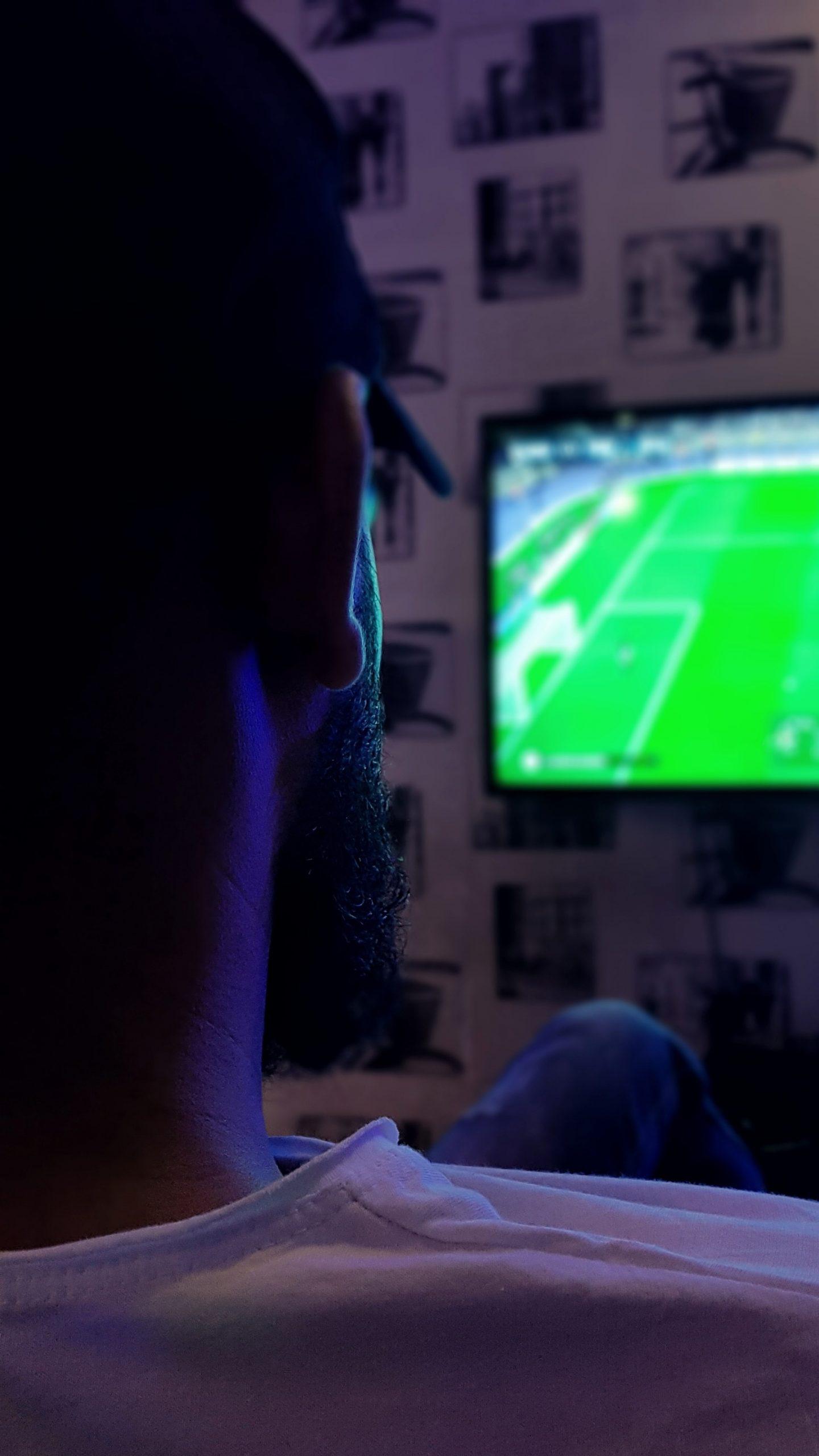 man watching football in the dark